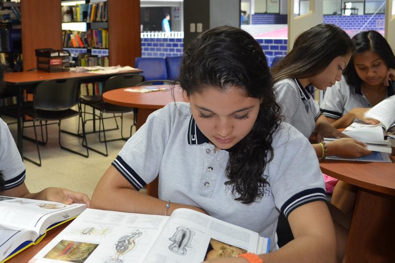 Mujer con playera gris sentada leyendo un libro dentro de una biblioteca de la preparatoria Acapulco