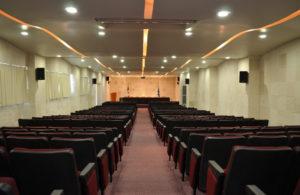Auditorio con luces, cortinas, bocinas negras y sillas en color negro con vino , mesa y banderas al fondo