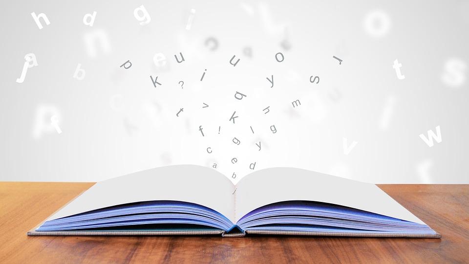Libro blanco sobre una mesa con letras saliendo de el