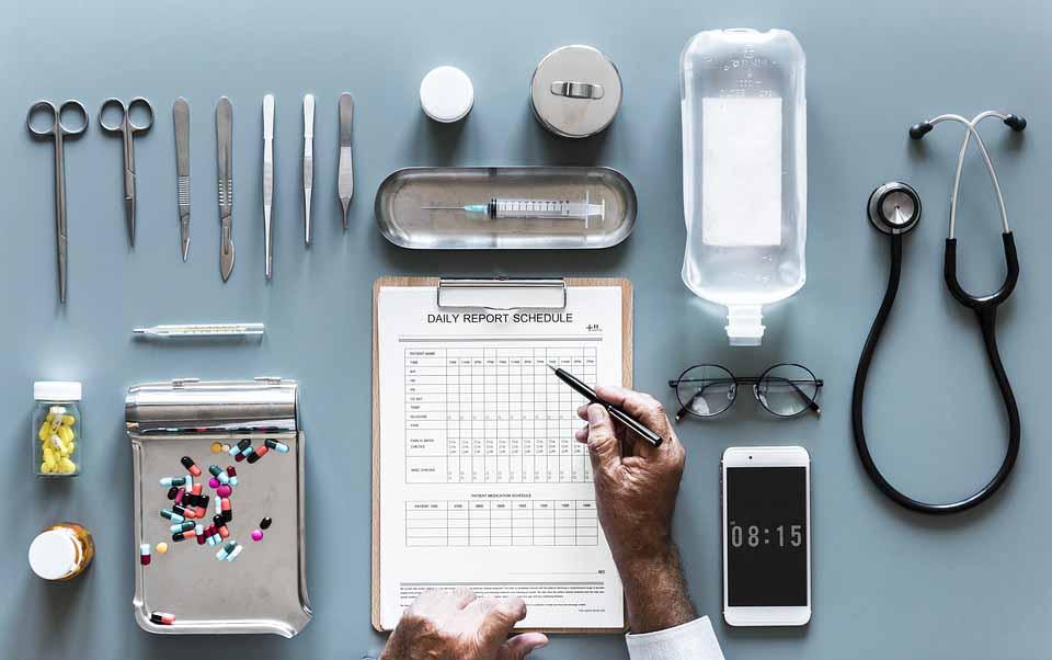 Hojas y pastillas con diferentes instrumentos de un médico sobre una mesa