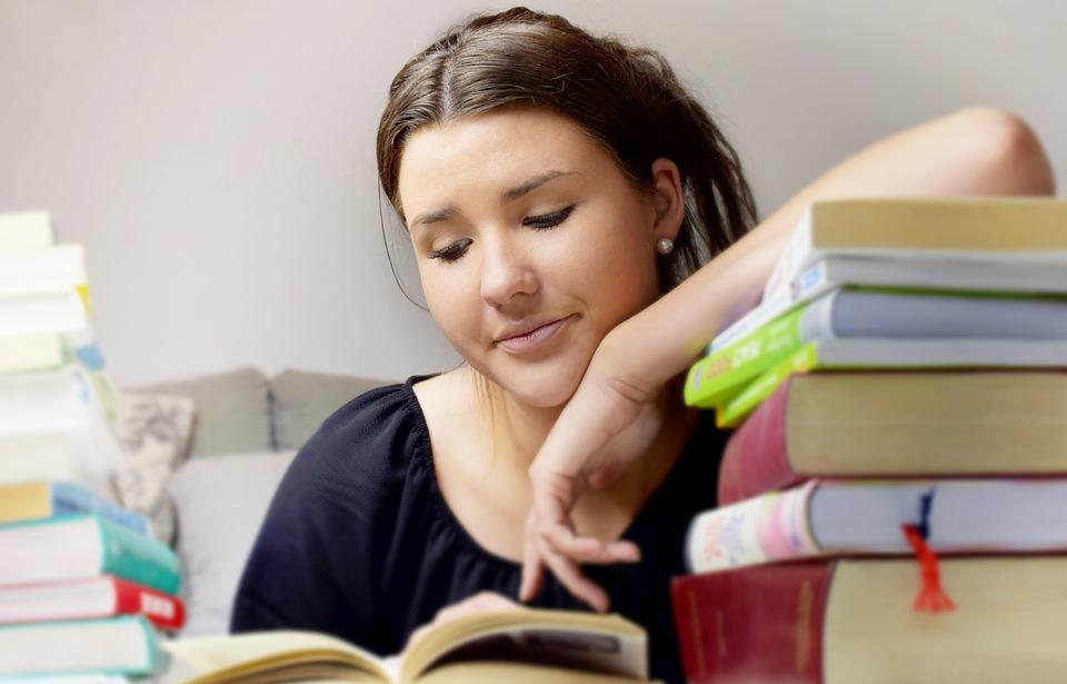 Mujer recargada sobre libros leyendo sobre un intercambio estudiantil en Acapulco
