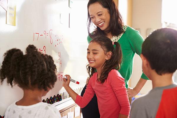 Mujer y niños escribiendo en un pizarrón blanco