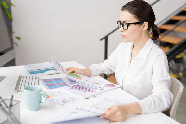 Mujer con blusa blanca sentada frente a un escritorio revisando papeles con gráficas