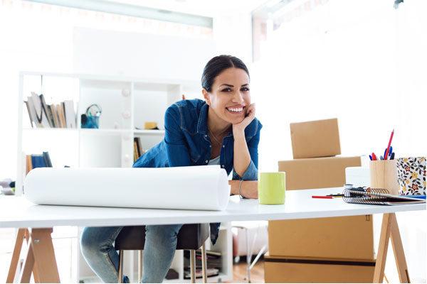 Mujer con blusa azul sonriendo recargada sobre un escritorio con cajas y papeles