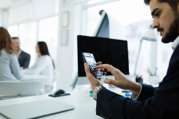 Hombre con traje negro sentado frente a un escritorio con un celular en las manos