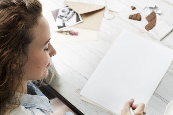 Mujer sentada frente a un escritorio escribiendo en unas hojas