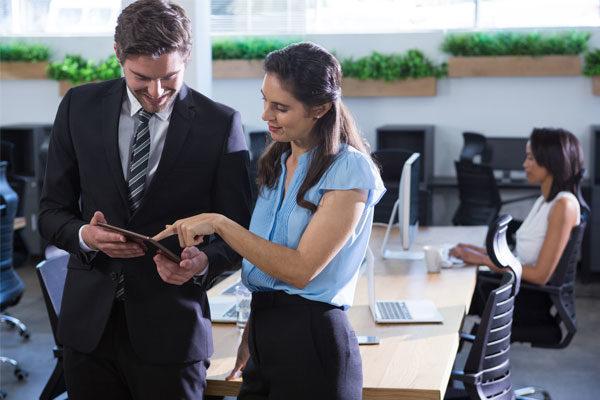 Hombre con traje negro y camisa y camisa blanca junto a una mujer con blusa azul y pantalón negro revisando una tablet