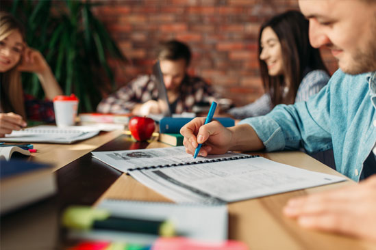 Ciencias sociales jóvenes escribiendo en cuaderno