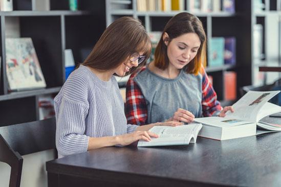 Mujeres jóvenes en biblioteca con libros