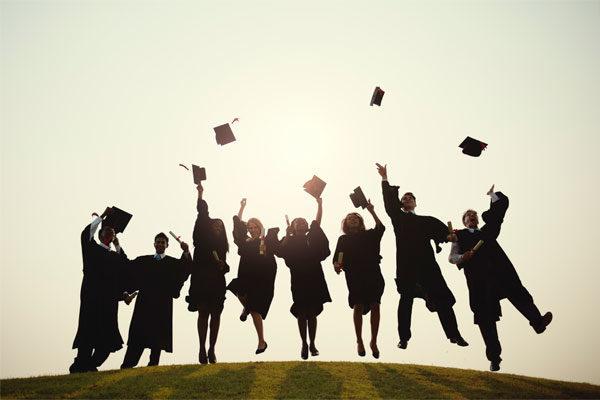 Grupo de estudiantes vistiendo toga y lanzando birrete al aire