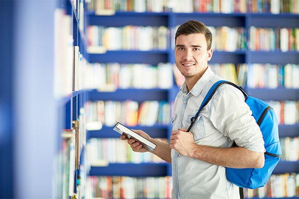Hombre joven sonriendo sosteniendo un libro