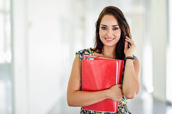 Mujer joven sonriendo cargando cuadernos color rojo
