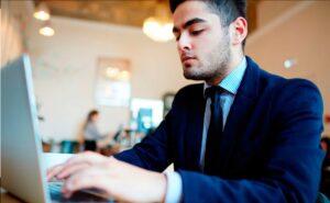 Hombre en traje sentado escribiendo en una laptop