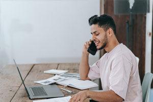 hombre hablando por teléfono viendo papeles