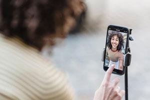 Mujer joven presionando el botón para grabar video en móvil